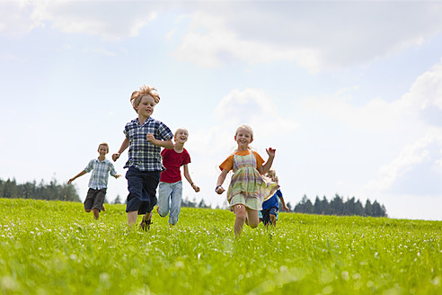 Germany, Bavaria, Group of children running through meadow - HSIYF000031