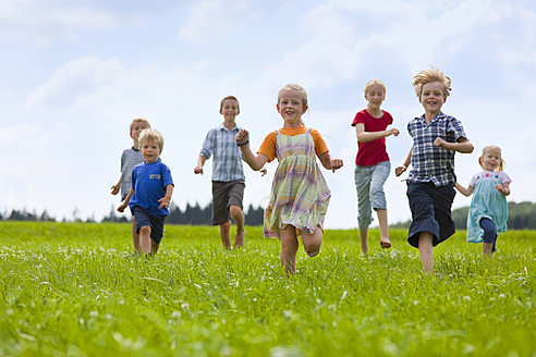Germany, Bavaria, Group of children running through meadow - HSIYF000034
