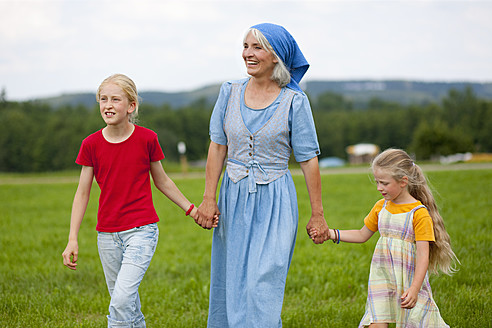 Germany, Bavaria, Grandmother with children walking through meadow - HSIYF000037