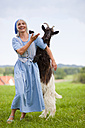 Germany, Bavaria, Mature woman playing with goat on farm - HSIYF000060