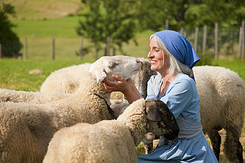 Germany, Bavaria, Mature woman playing with sheep on farm - HSIYF000063