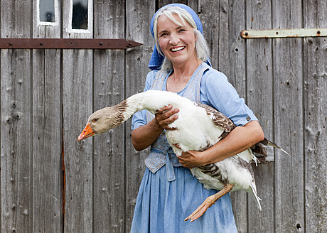 Germany, Bavaria, Mature woman with goose on farm - HSIYF000069