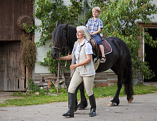 Germany, Bavaria, Mature woman leading boy on horse - HSIYF000073