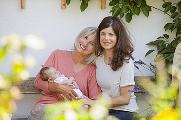Germany, Bavaria, Three generations sitting together, smiling - HSIYF000090