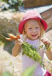 Germany, Bavaria, Girl picking carrots in garden - HSIYF000127