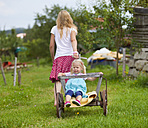 Germany, Bavaria, Mother pulling daughter in hand cart through meadow - HSIYF000142