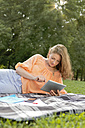 Germany, Berlin, Young student learning in Treptower Park with tablet - FKF000070