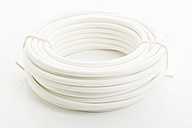 Close up of rolled electric cable on white background - MAEF005042