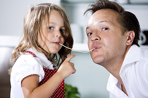 Germany, Daughter eating noodles with father in kitchen - RFF000054