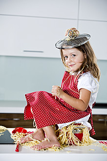 Germany, Girl playing with spaghetti on kitchen worktop - RFF000075