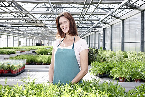Germany, Bavaria, Munich, Mature woman in greenhouse with rocket plants - RREF000001
