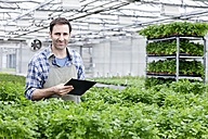 Germany, Bavaria, Munich, Mature man in greenhouse between parlsey plants with clip board - RREF000026