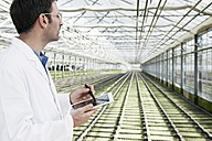 Germany, Bavaria, Munich, Scientist in greenhouse with digital tablet examining bed with seedlings - RREF000054