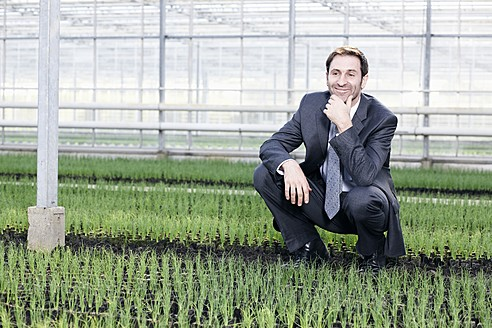Germany, Bavaria, Munich, Mature man in greenhouse between seedlings - RREF000079