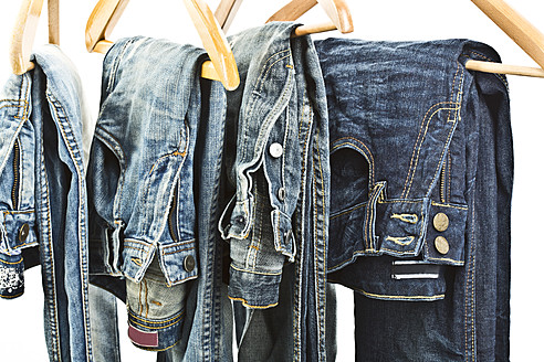 Close up of blue jeans on coathangers - MAEF005020