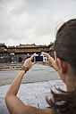Vietnam, Hue, Young woman taking photograph of Hue Citadel - MBEF000522