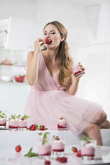 Germany, Young woman biting strawberry, glasses with strawberry yogurt - RFMYF000042