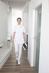 Germany, Dentist walking with clip board - FMKYF000181