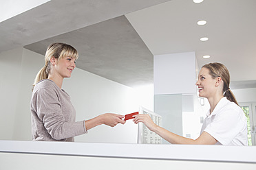 Germany, Patient giving insurance card to receptionist in dental office - FMKYF000193
