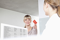 Germany, Patient giving insurance card to receptionist in dental office - FMKYF000196
