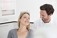 Germany, Dentist and patient in clinic, smiling - FMKYF000208