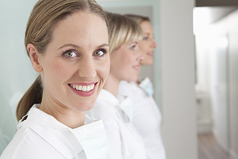Germany, Dentist and assistance, smiling - FMKYF000238