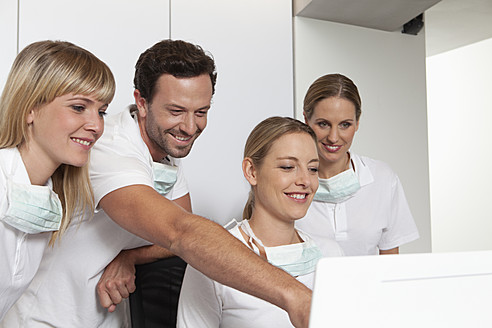 Germany, Dentist and assistance looking at screen - FMKYF000244
