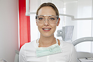 Germany, Dentist with safety glasses in dental office - FMKYF000253