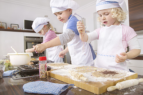 Germany, Girls and boy baking cup cakes and pouring sugar sprinkles - FKF000090