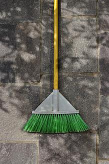 Germany, Broom laying on pavement - AXF000292