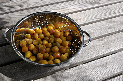 Germany, Baden Wuerttemberg, Yellow plums in colander on wooden table - AXF000307
