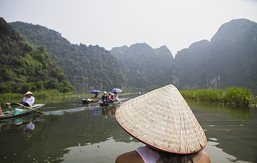 Vietnam, Ninh Binh, Young tourist on river boar in Tom Coc - MBEF000528