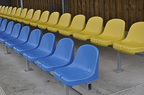 Germany, Bavaria, Munich, Stand with blue and yellow plastic seats - AXF000330