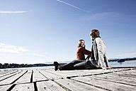 Germany, Bavaria, Couple sitting on jetty at Lake Starnberg - RBF001054