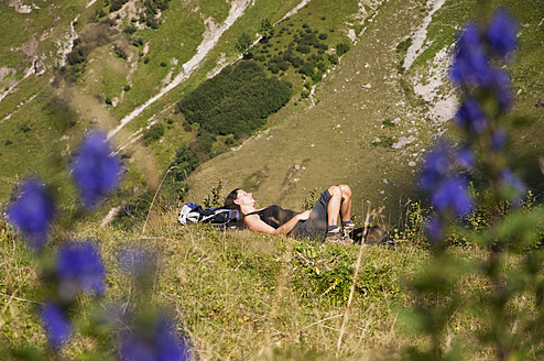 Austria, Mid adult woman relaxing on mountain - UMF000556