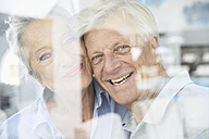 Spain, Senior couple behind window, smiling - PDYF000178