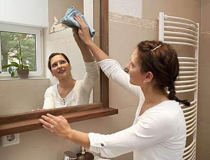 Germany, Brandenburg, Young woman cleaning mirror in bathroom - BFRF000113