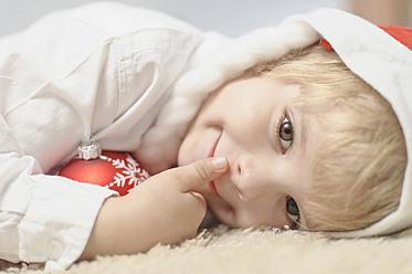Boy holding christmas bauble, smiling, portrait - MJF000150