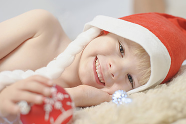 Boy holding christmas bauble, smiling, portrait - MJF000145