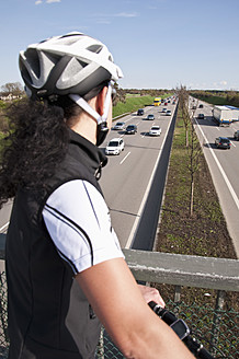 Germany, Mid adult woman with mountain bike on bridge looking at traffic on highway - UMF000512