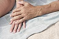 Spain, Mallorca, Senior couple holding hands at beach - PDYF000277