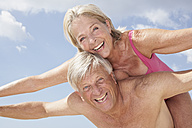 Spain, Senior man giving piggy back ride to woman - PDYF000268