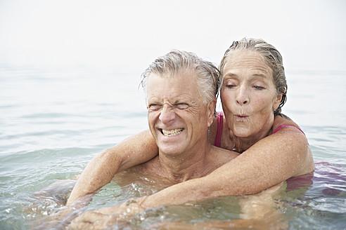 Spain, Senior couple swimming in sea - PDYF000235