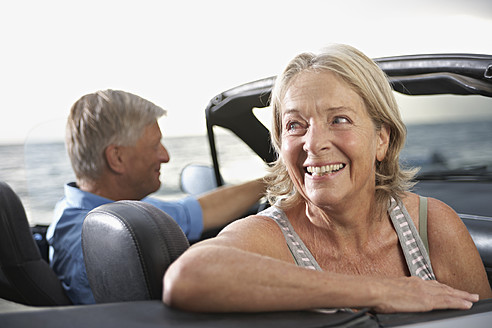 Spain, Senior couple in convertible car, smiling - PDYF000229