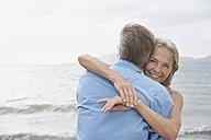 Spain, Mallorca, Senior couple embracing on beach - PDYF000217