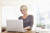 Germany, Bavaria, Munich, Woman using laptop, smiling - RBYF000245