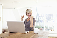 Germany, Bavaria, Munich, Woman happy while using laptop - RBYF000247