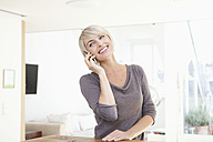 Germany, Bavaria, Munich, Woman using mobile phone, smiling - RBYF000327