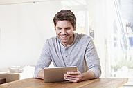 Germany, Bavaria, Munich, Man using digital tablet at table - RBYF000276