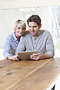 Germany, Bavaria, Munich, Mature couple using digital tablet, smiling - RBYF000279